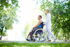 nurse walking with male patient in a wheelchair in park